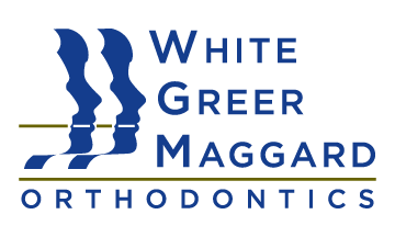 White, Greer, and Maggard Orthodontics logo in blue letters and gold accents.